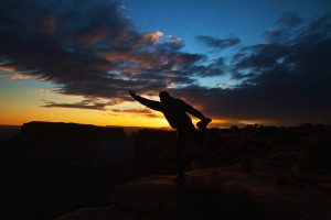 Image of man doing yoga on a cliff